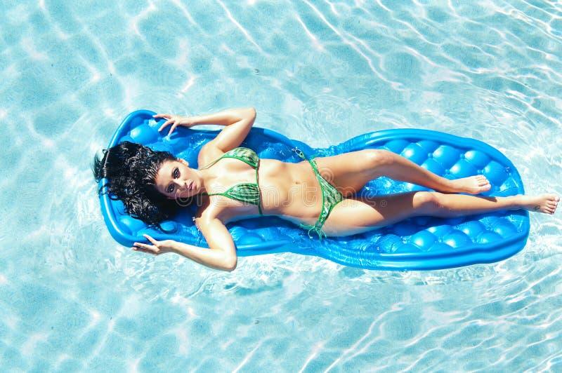 比基尼泳装浮动的池妇女 图库摄影