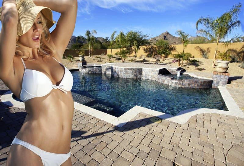 比基尼泳装白肤金发的女性游泳池边 库存照片