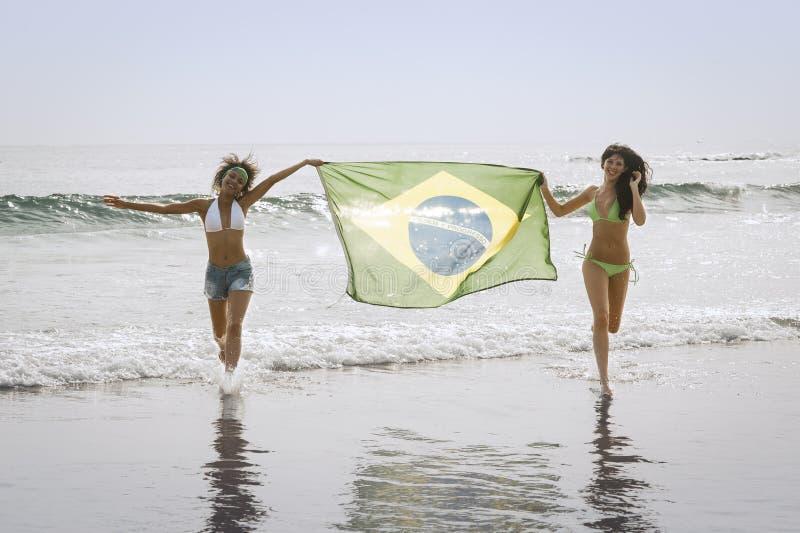 比基尼泳装的两名年轻美丽的妇女在跑与巴西旗子的海滩 免版税库存图片