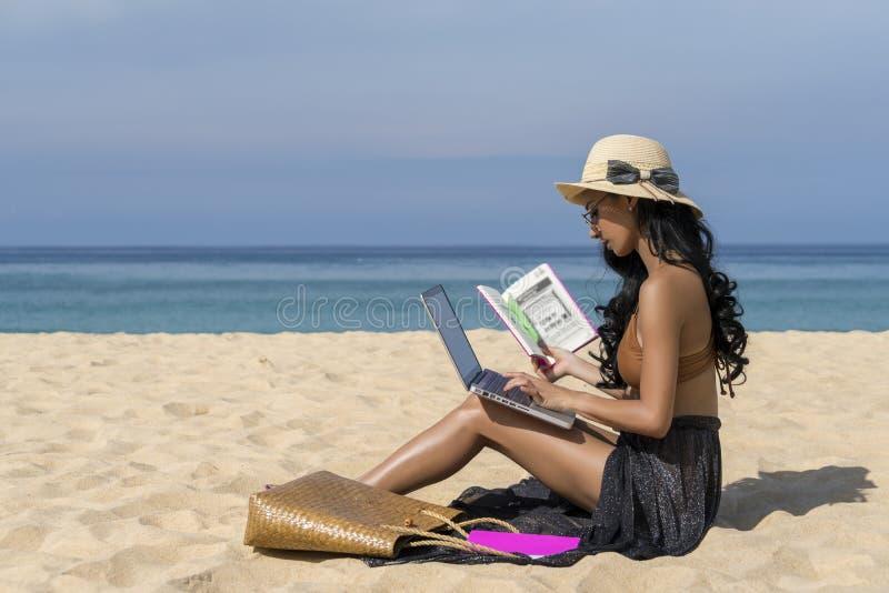 比基尼泳装的亚裔性感的妇女,使用手提电脑和举行书在海滩,暑假旅行  自由职业者的工作概念 免版税图库摄影