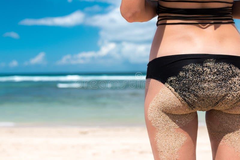 黑比基尼泳装的亭亭玉立的豪华女孩在海滩 罕见的看法 完善被晒黑的身体,性感的驴子,完善的图 a的基于 库存照片