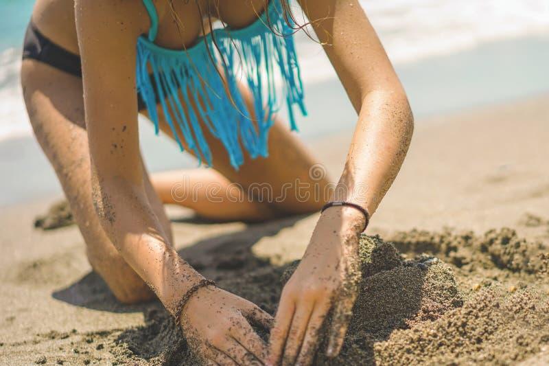 比基尼泳装的俏丽的女孩修造在海滩的沙子城堡 免版税库存照片