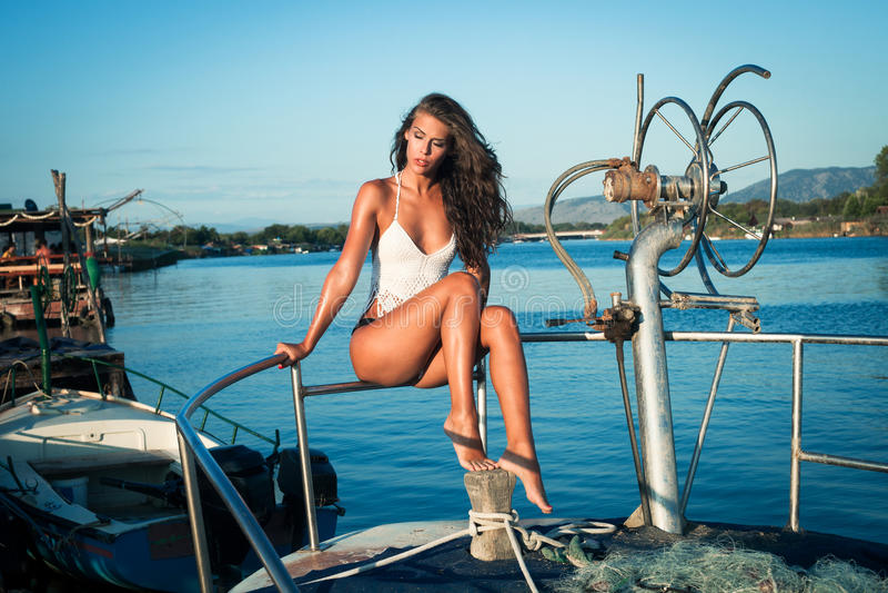 比基尼泳装的俏丽的妇女在小船 库存图片