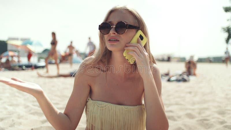 比基尼泳装的俏丽的妇女谈话在电话在海滩 免版税库存照片