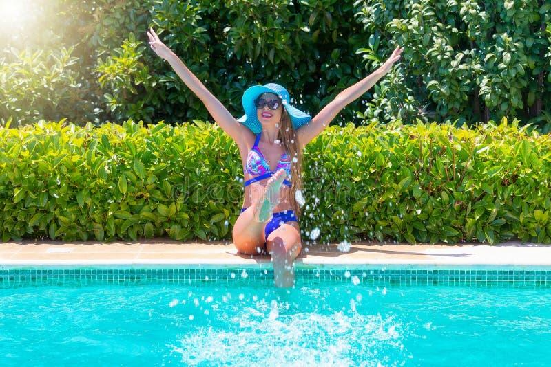 比基尼泳装的可爱的妇女获得乐趣在游泳池边 免版税库存照片