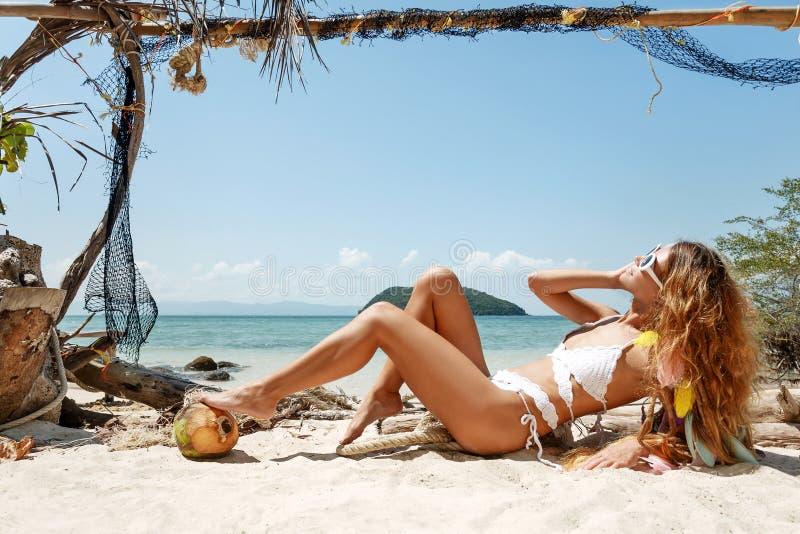 比基尼泳装的可爱的少妇在海滩 免版税库存图片