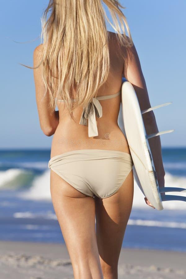 比基尼泳装的女子冲浪者与在海滩的冲浪板 免版税库存图片