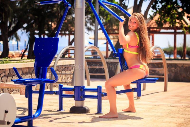 比基尼泳装的女孩坐健身模拟器微笑在公园 库存照片