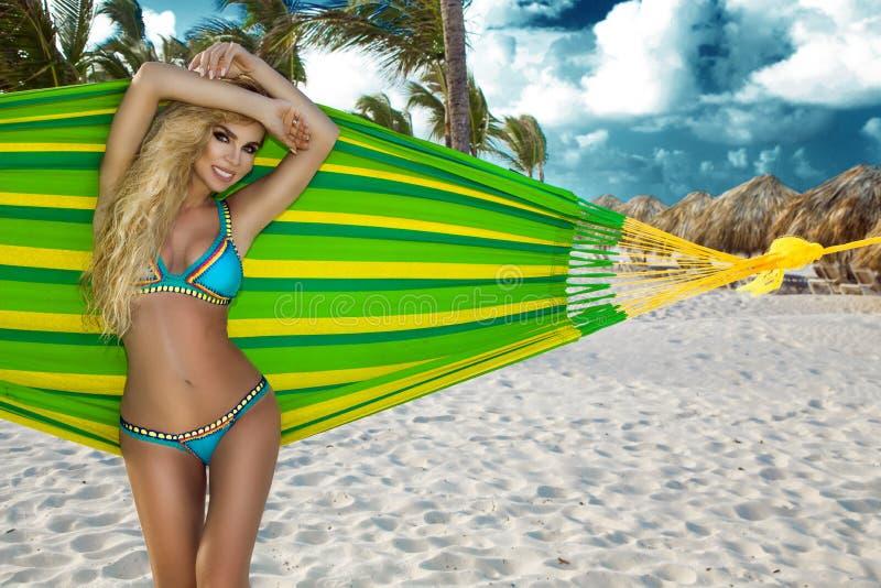 比基尼泳装的女孩用坐在加勒比海滩的吊床和享受日落的椰子 美丽的长的金发-图象 库存照片