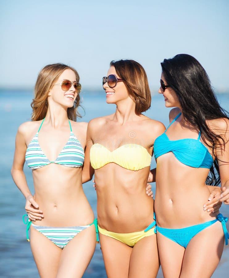 比基尼泳装的女孩走在海滩的 免版税图库摄影
