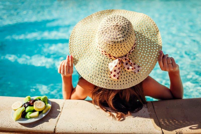 比基尼泳装的妇女吃果子和放松在游泳场的 所有包含 katya krasnodar夏天领土假期 库存照片