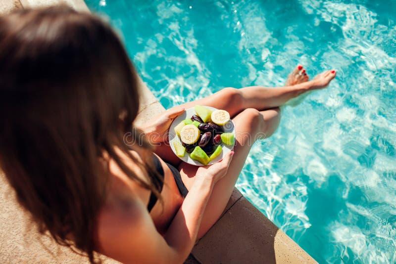 比基尼泳装的妇女吃果子和放松在游泳场的 所有包含 katya krasnodar夏天领土假期 免版税库存图片