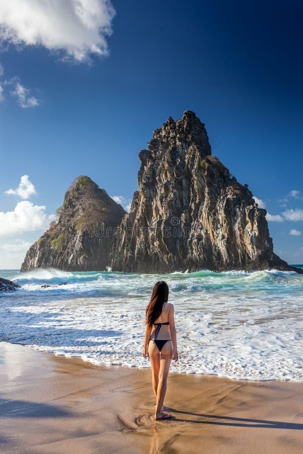 比基尼泳装的妇女在大岩石费尔南多・迪诺罗尼亚群岛,在巴西的东北部的小岛附近站立 库存图片