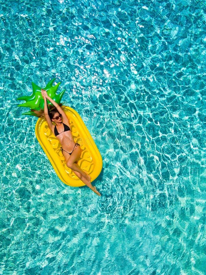 比基尼泳装的妇女在水池的一个菠萝被塑造的浮游物放松 免版税库存图片