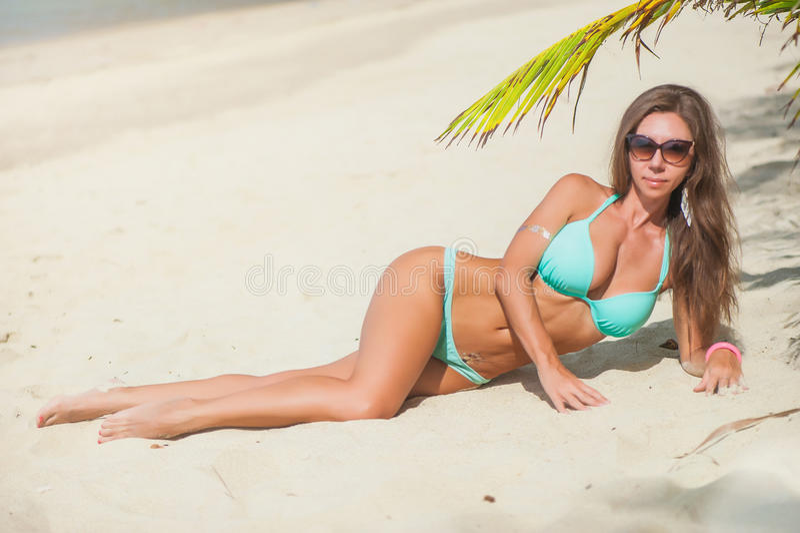 比基尼泳装的妇女在海背景的棕榈下 库存照片