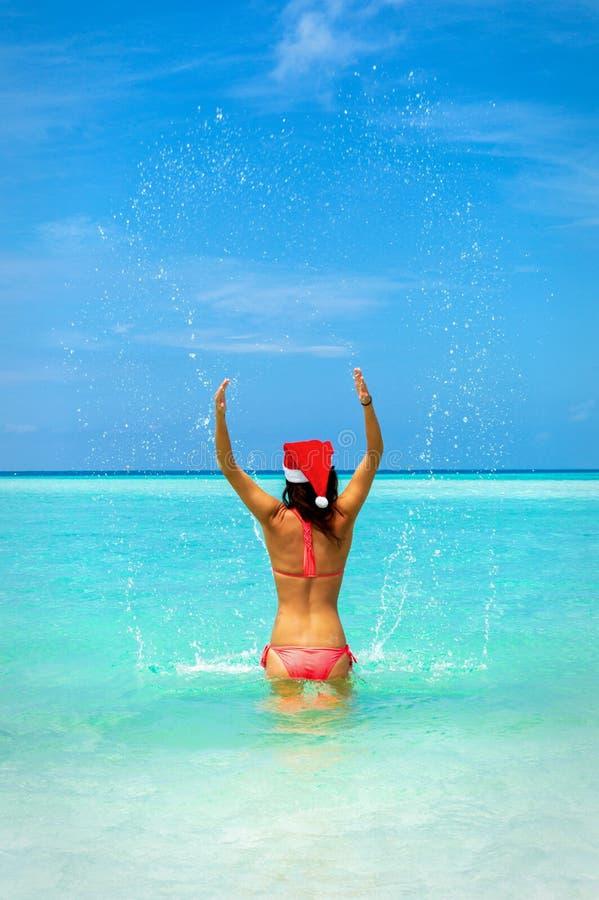比基尼泳装的妇女在绿松石海飞溅水 库存图片