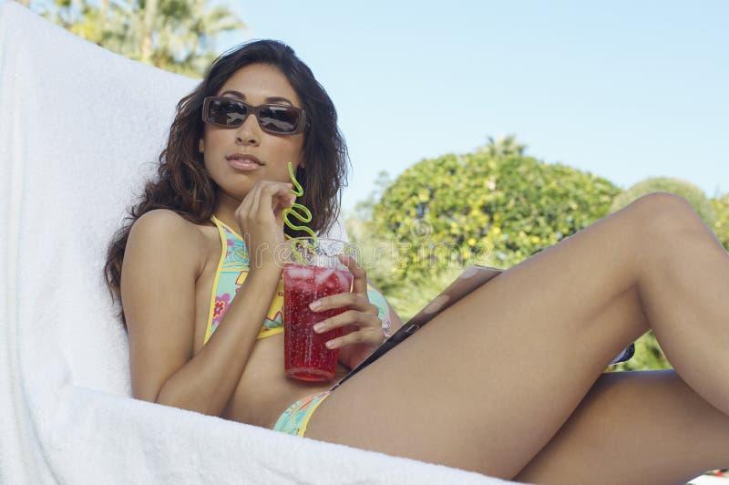 比基尼泳装的妇女坐与鸡尾酒的Deckchair 免版税库存照片