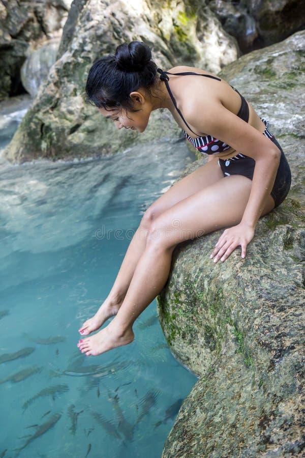 比基尼泳装的妇女坐岩石 免版税库存图片