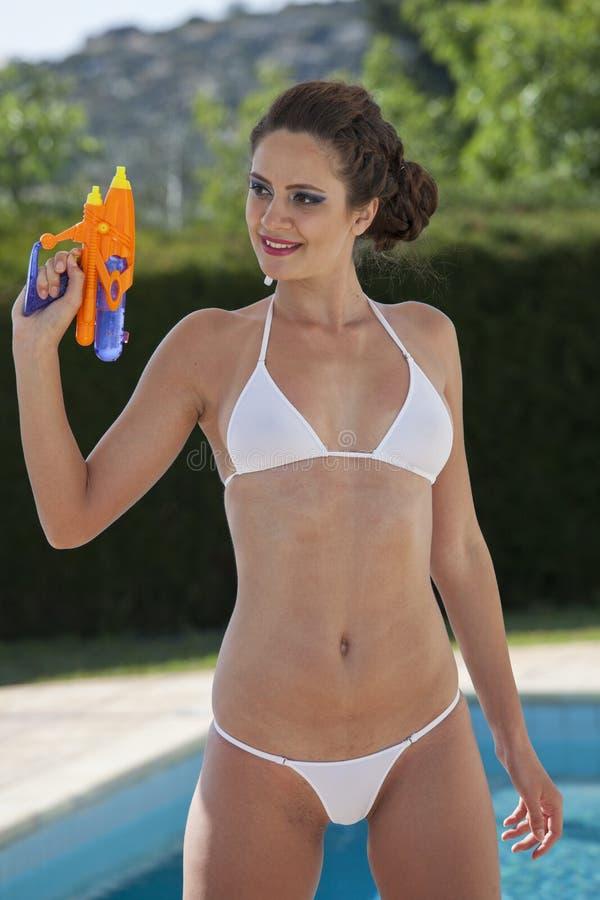 比基尼泳装的妇女有水枪的 免版税库存照片