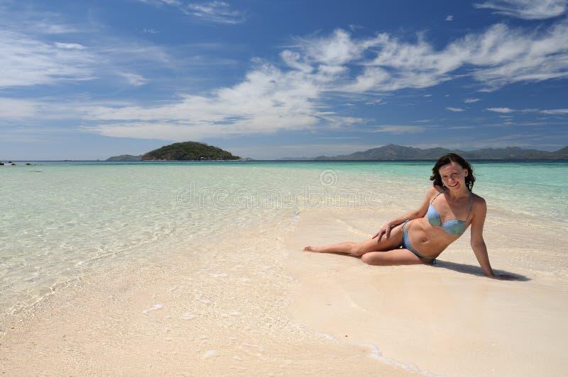 比基尼泳装的少妇在海滩 免版税库存图片