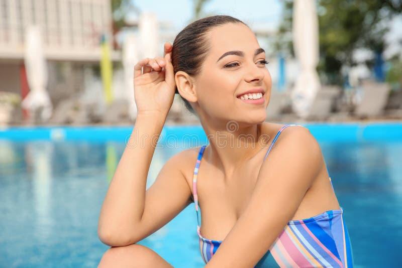 比基尼泳装的少妇在游泳池附近 免版税库存照片