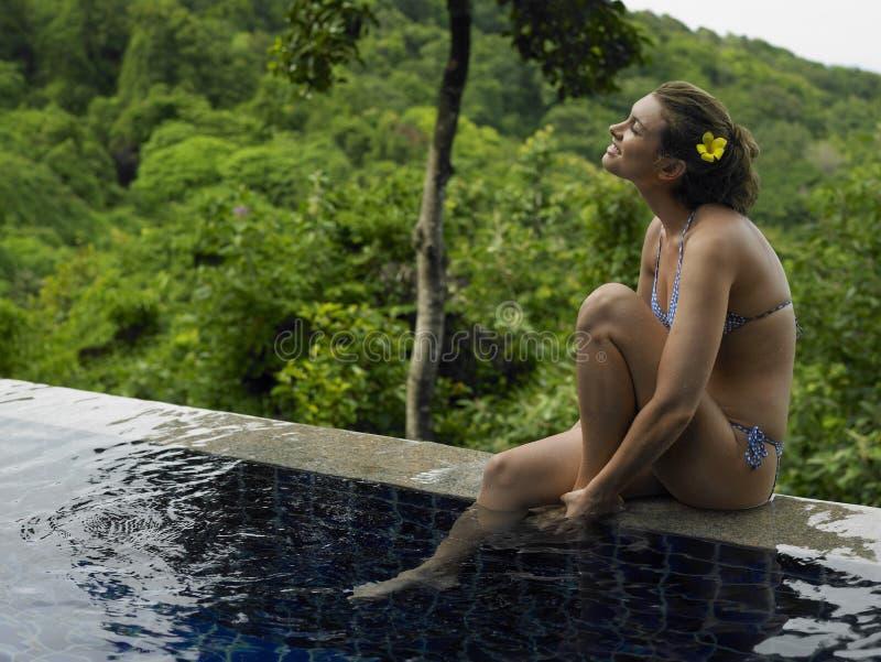 比基尼泳装的少妇由游泳池 免版税图库摄影