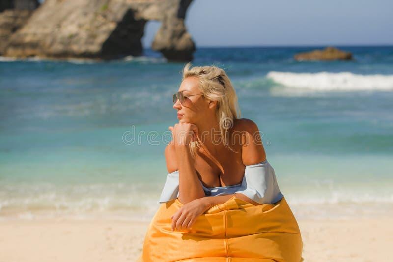 比基尼泳装的年轻可爱和轻松的白肤金发的妇女说谎在装豆子小布袋吊床在热带天堂海滩享受异乎寻常的夏天的 库存图片