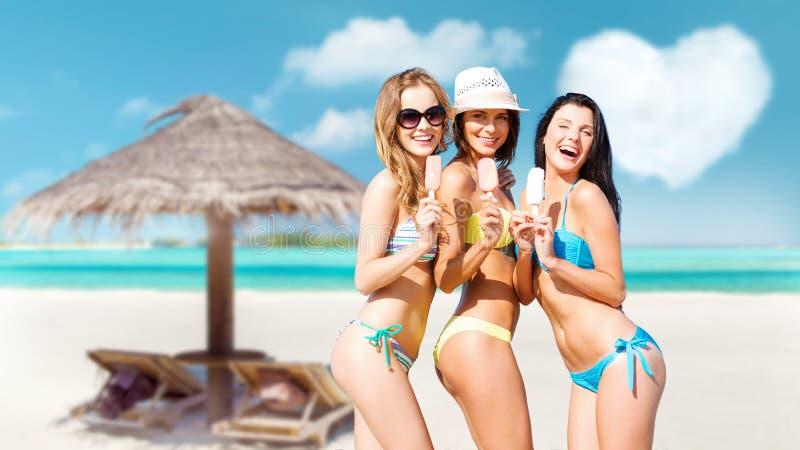 比基尼泳装的年轻女人有在海滩的冰淇淋的 库存照片