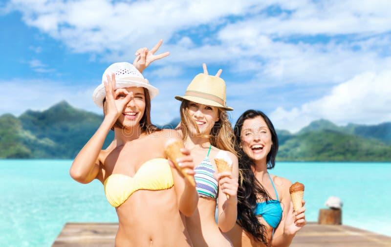 比基尼泳装的年轻女人有在海滩的冰淇淋的 免版税库存照片