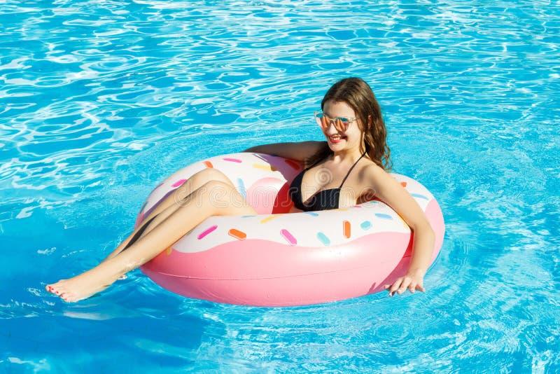 比基尼泳装的年轻愉快的女孩在与一个桃红色圈子的水池游泳 免版税库存照片