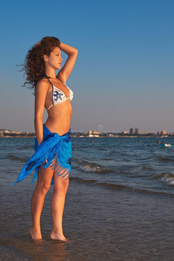 比基尼泳装的年轻美丽的亭亭玉立的被晒黑的妇女在海滩调查距离 免版税库存图片