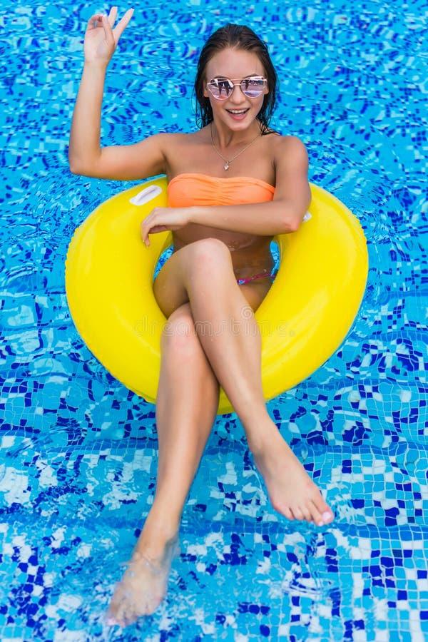 比基尼泳装的性感的妇女享用夏天太阳和晒黑在水池的假日期间的 顶视图 池游泳妇女 biki的性感的妇女 免版税库存图片