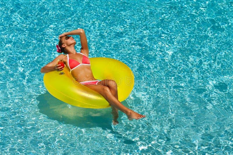 比基尼泳装的性感的妇女享用夏天太阳和晒黑在水池的假日期间的 免版税图库摄影