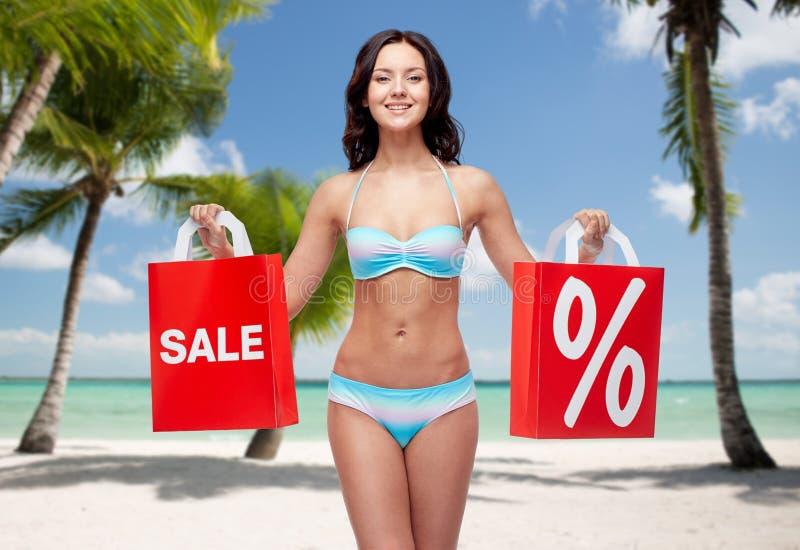 比基尼泳装的愉快的妇女有在海滩的购物袋的 库存照片