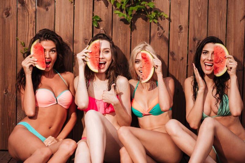 比基尼泳装的愉快的美丽的女孩吃西瓜的在水池 免版税库存图片