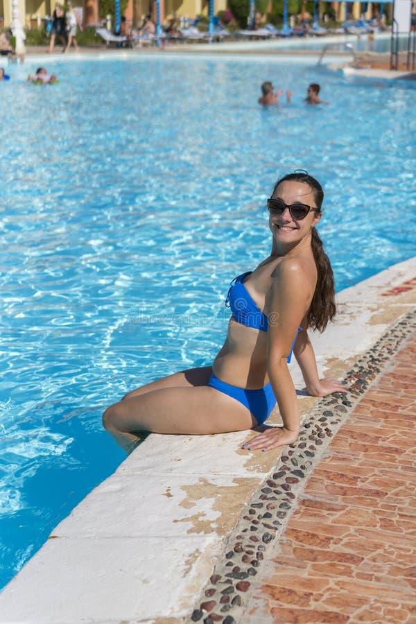 比基尼泳装的愉快,年轻美女坐游泳场边缘,户外 有放松的美女在水池附近 温泉 免版税库存图片