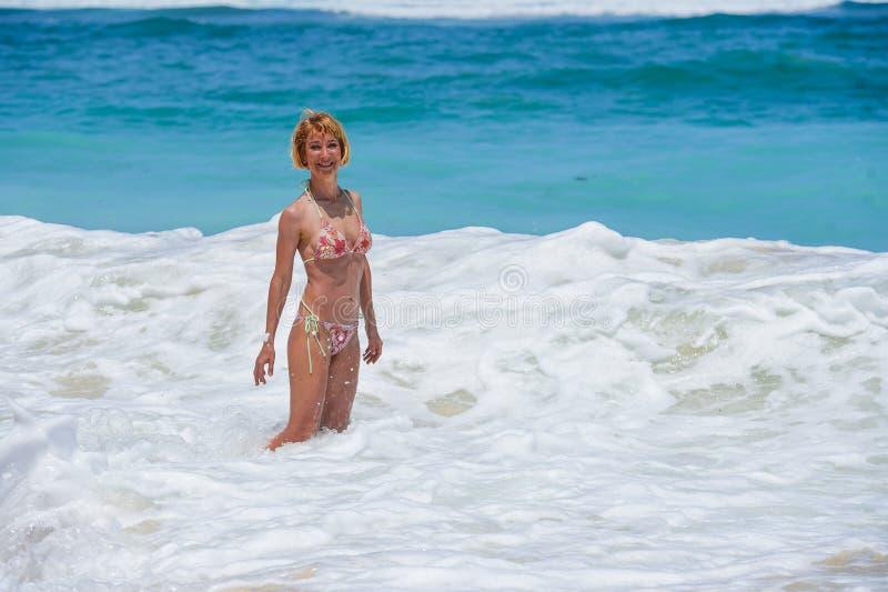 比基尼泳装的摆在使与大波浪的美丽的沙漠海滩惊奇享受夏天的年轻可爱和愉快的妇女画象ho 库存照片