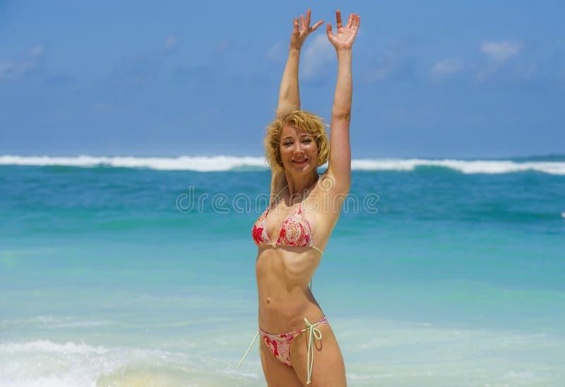 比基尼泳装的摆在使美丽的沙漠海滩惊奇举胳膊任意享用Summe的年轻可爱和愉快的妇女画象  免版税图库摄影