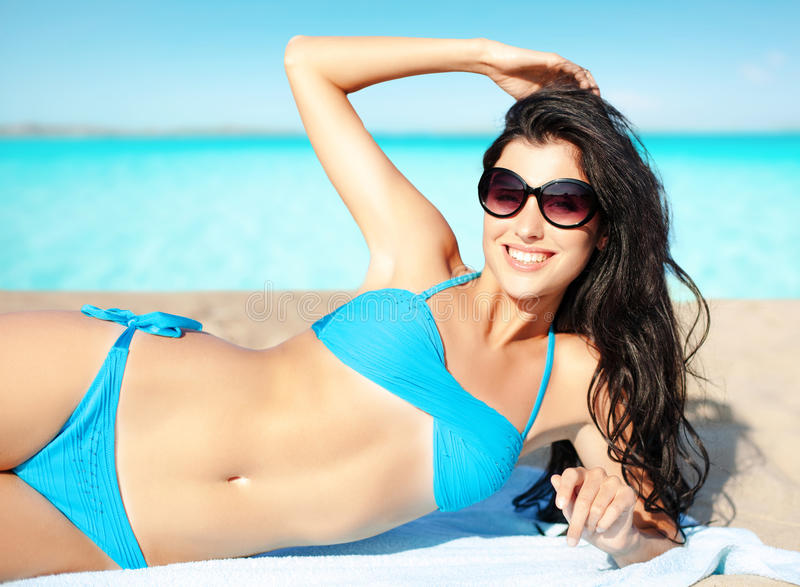 比基尼泳装的晒日光浴在海滩的妇女和树荫 库存图片
