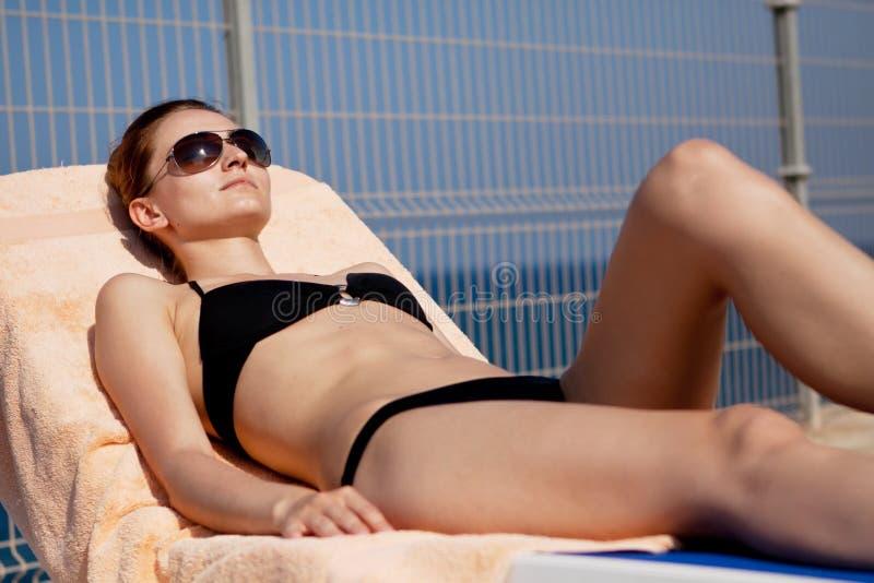 比基尼泳装的晒日光浴性感的妇女在sunlounger放松 库存照片
