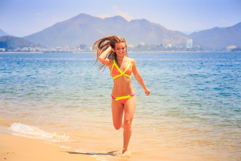 比基尼泳装的白肤金发的亭亭玉立的女孩做在海飞溅反对小山 免版税库存图片