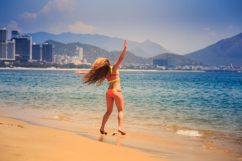 比基尼泳装的白肤金发的亭亭玉立的女孩表现出在天蓝色的海边缘的喜悦  库存图片