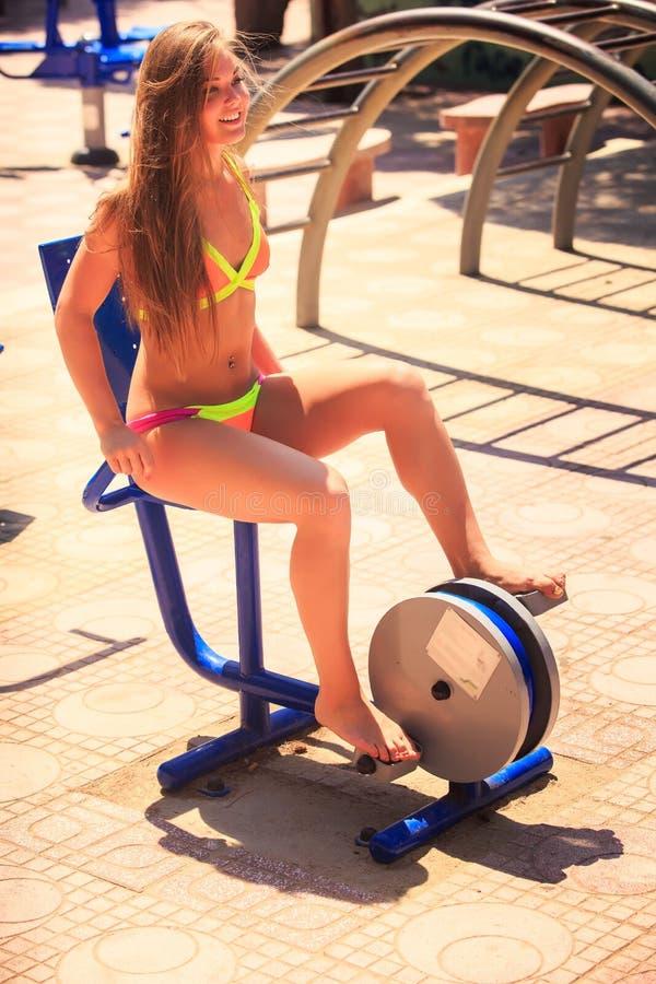 比基尼泳装的白肤金发的女孩坐室外自行车模拟器微笑 库存照片