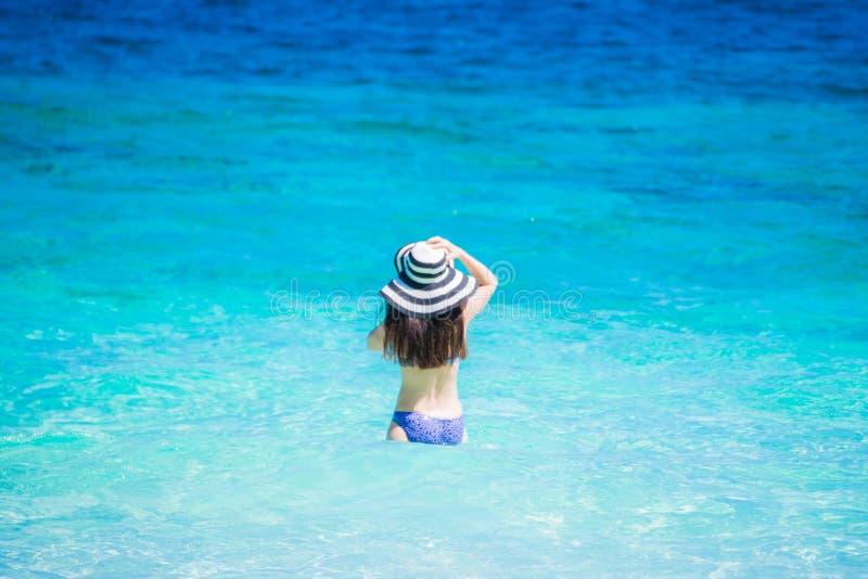 比基尼泳装的美丽的夫人有帽子的享受暑假 免版税库存照片