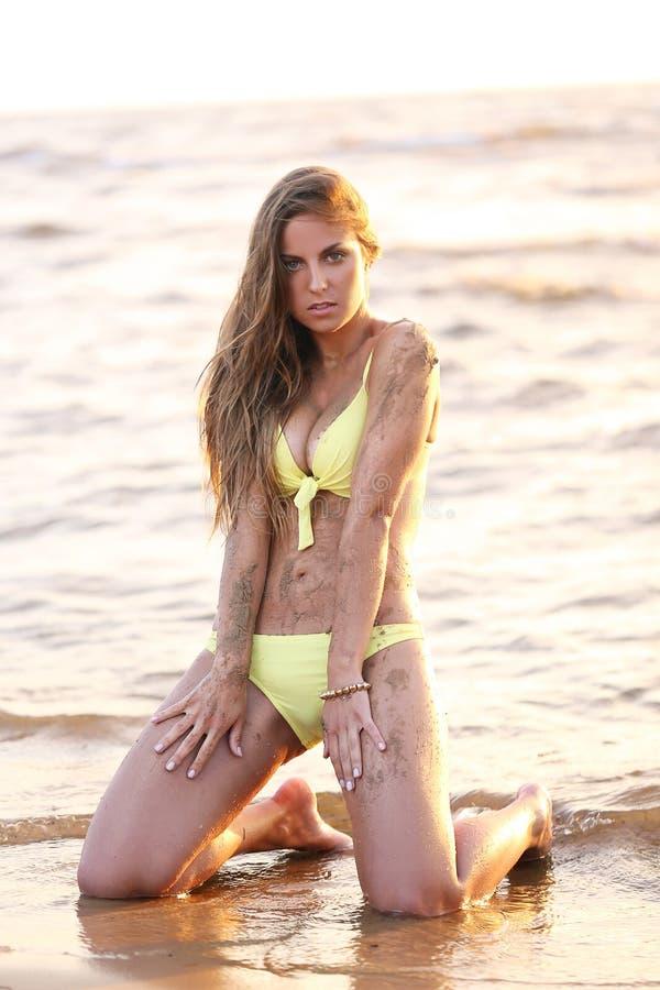 比基尼泳装的美丽的女孩在海滩 免版税库存照片