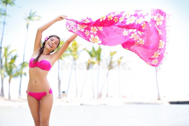 比基尼泳装的美丽的妇女在海滩挥动的围巾 免版税库存图片