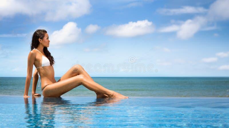 比基尼泳装的美丽的妇女晒日光浴在海边的 免版税库存照片