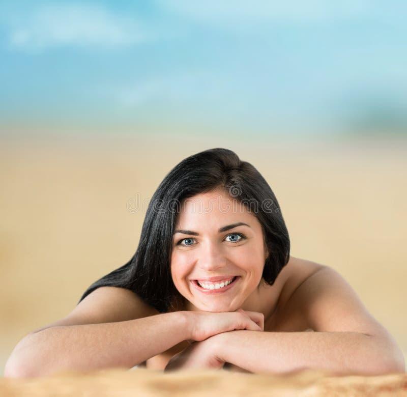 比基尼泳装的美丽的妇女晒日光浴在海边的 库存图片