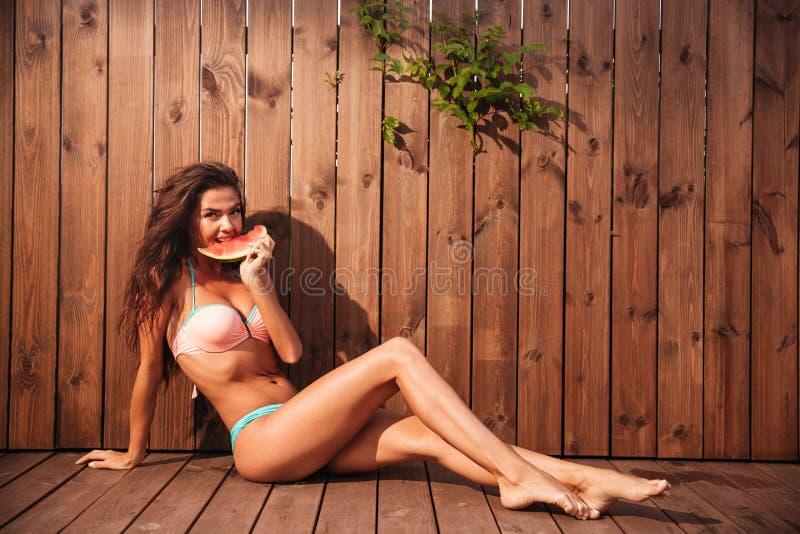 比基尼泳装的美丽的少妇吃在木背景的西瓜 图库摄影