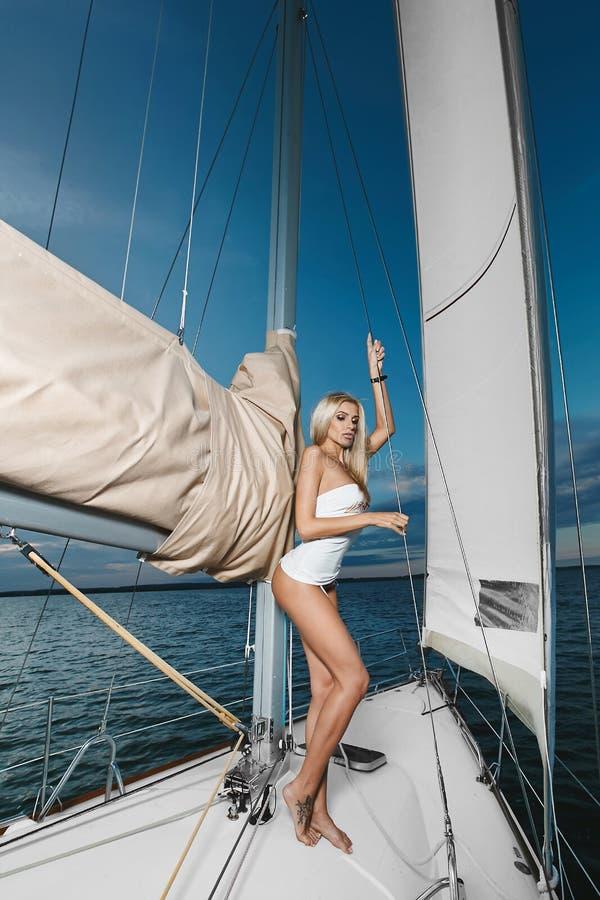 比基尼泳装的美丽的时兴的白肤金发的摆在游艇的女孩和T恤杉运送 图库摄影